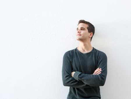 human arm: Portrait of a young man standing against white with arms folded Stock Photo