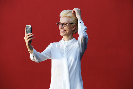 glasses model: Portrait of a smiling young blond woman taking selfie