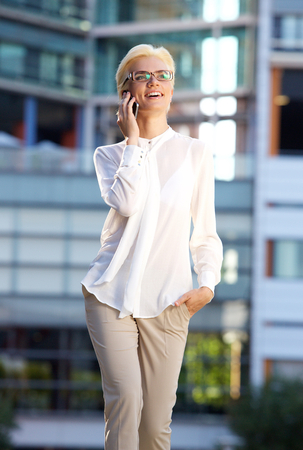 business woman working: Portrait of a smiling business woman walking outside with mobile phone Stock Photo