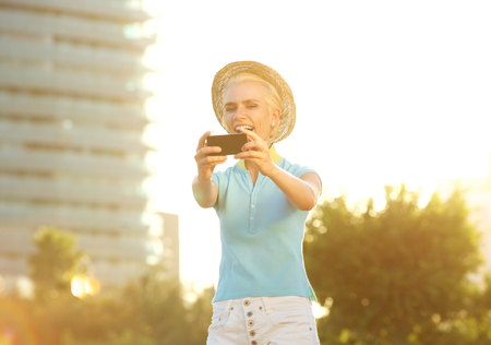 happy smiling: Happy smiling young woman with hat taking selfie portrait outside