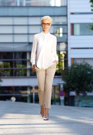 glasses model: Full length portrait of an elegant young fashion woman walking outside Stock Photo
