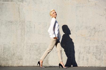 Full body side portrait of a smiling female fashion model walking Zdjęcie Seryjne - 43923703