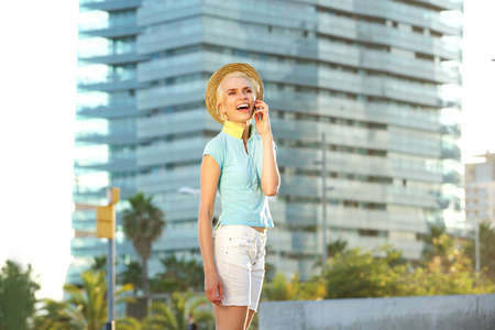 femme blonde: Portrait of a cheerful young woman talking on mobile phone in the city Banque d'images