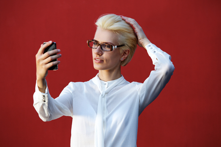 glasses model: Portrait of a beautiful blond woman looking at mobile phone and checking her hair