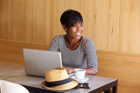 Portret van een jonge zwarte vrouw glimlachend en met behulp van laptop Stockfoto