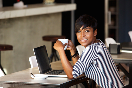 mujer pensando: Retrato de una mujer afroamericana se relaja en el café con el ordenador portátil y el café Foto de archivo