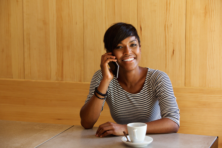 Portrait of a smiling black woman listening to mobile phone call at cafe Stock Photo
