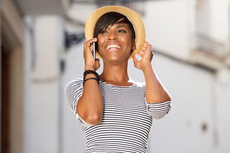 Portret van een vrolijke jonge zwarte vrouw die op mobiele telefoon Stockfoto