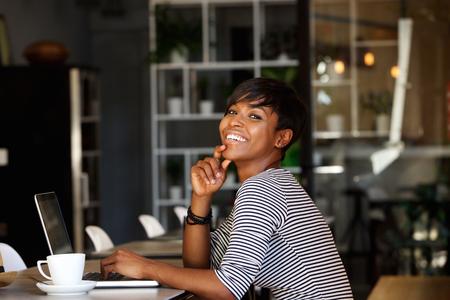 femmes souriantes: Portrait de côté d'un sourire jeune femme afro-américaine assis à un café avec un ordinateur portable