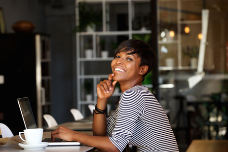business profiles: Side portrait of a smiling young african american woman sitting at cafe with laptop