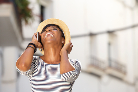 woman in black: Portrait of a happy young woman laughing with cell phone