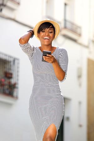 fond de texte: Portrait d'une jeune femme noire lecture message texte souriant sur t�l�phone portable