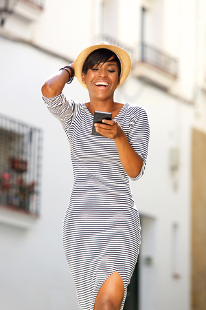 cell: Portrait of a smiling young black woman reading text message on cell phone