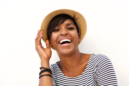Close up portrait of an attractive young black woman smiling with hat against white background