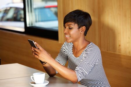 mecanografía: Retrato de un mensaje africano americano Joven y bella mujer de lectura de texto en el teléfono móvil