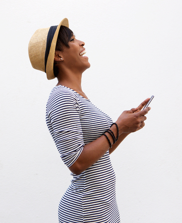 holding: Side portrait of a young woman laughing and holding mobile phone Stock Photo