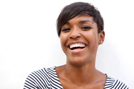 afroamericanas: Cerca de retrato de una hermosa mujer afroamericana que ríe en el fondo blanco Foto de archivo
