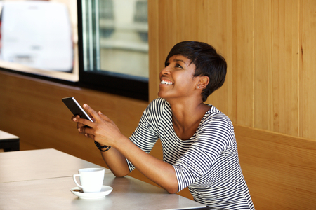 mobile internet: Portrait of a young african american woman laughing with mobile phone