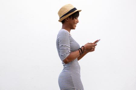 Side Porträt einer fröhlichen jungen Frau zu Fuß und SMS