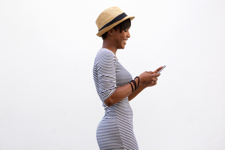 Side portrait of a cheerful young woman walking and texting
