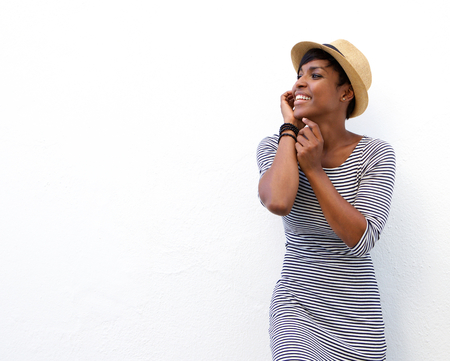 single: Portrait of a happy black woman smiling with hat against white background Stock Photo