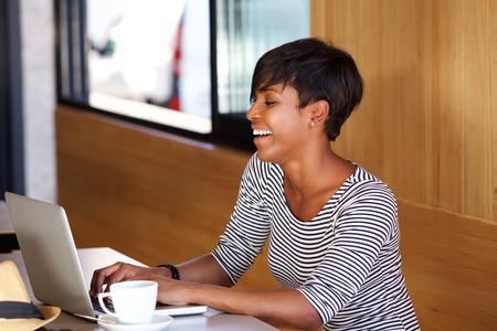 cafe internet: Retrato de una joven mujer afroamericana utilizando el ordenador portátil sonriente