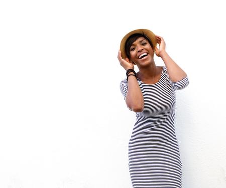 Portrait eines lächelnden African American Mode Modell posiert mit Hut vor weißem Hintergrund