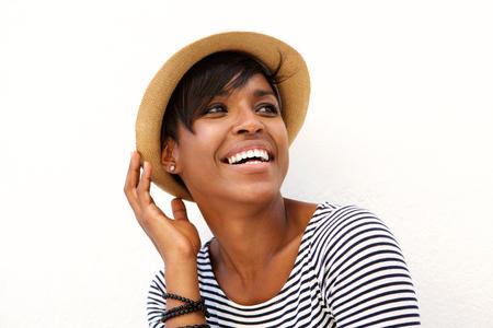 Schließen Sie herauf Porträt von einer schwarzen Frau, die mit Hut gegen weißen Hintergrund lächelt Standard-Bild