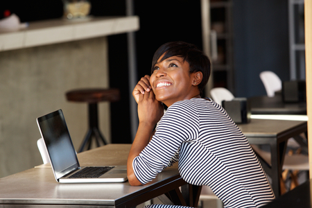 Side portrait of a cheerful young woman sitting at cafe with laptop