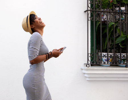 americans: Profile portrait of a laughing young woman walking with mobile phone