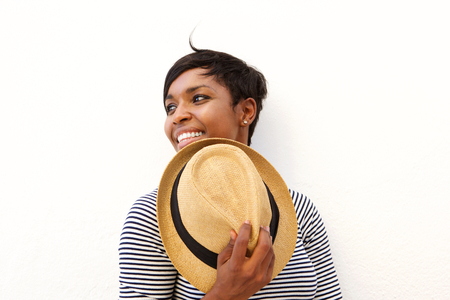 white face: Close up portrait of a smiling black woman holding hat