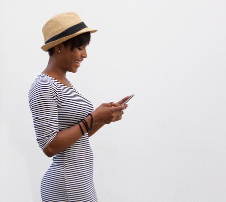 negras africanas: Retrato lateral de una sonriente mujer afroamericana caminar y leer mensajes de texto Foto de archivo