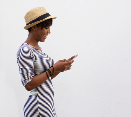 pretty black woman: Side portrait of a smiling african american woman walking and reading text message Stock Photo