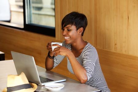 tomando café: Retrato de una mujer de tomar café americano africano sonriente y mirando portátil Foto de archivo