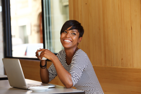 Portrait of a smiling young black woman with coffee and laptop at cafe Reklamní fotografie