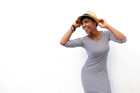 riendose: Retrato de una atractiva mujer de negro sonriendo con sombrero contra el fondo blanco Foto de archivo