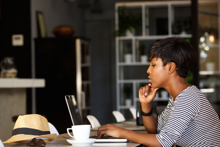 Side portrait of an african american woman using laptop at cafe restaurant