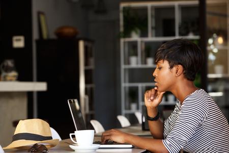 Side Porträt eines afroamerikanischen Frau mit Laptop im Café Restaurant Lizenzfreie Bilder
