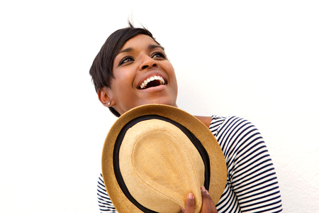laughing face: Close up portrait of an attractive african american woman holding hat