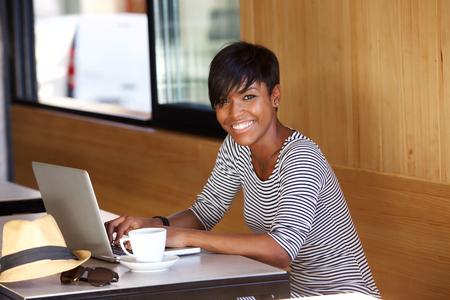 schwarz: Porträt einer lächelnden jungen schwarzen Frau mit Laptop