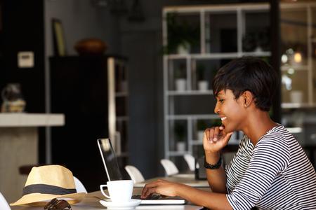 Side Porträt einer jungen Afroamerikanerfrauenlächeln im Kaffee mit Laptop