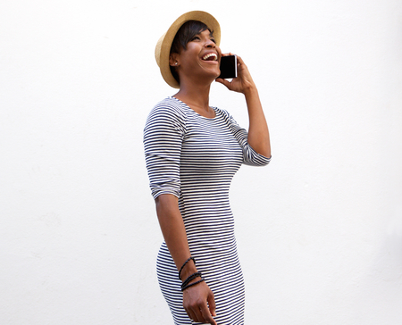 Side portrait of a smiling young woman walking and talking on cell phone Stock Photo