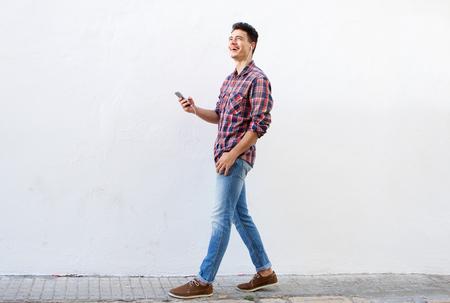 cuerpo hombre: Retrato de cuerpo entero lado de un hombre que camina sonriendo y escuchar música en el teléfono móvil