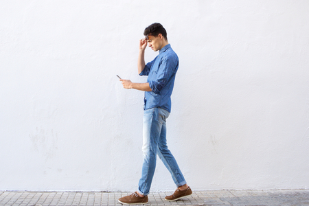 Full body portrait of a young man walking and reading text message on cell phone 스톡 콘텐츠