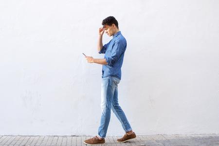 caminando: Retrato de cuerpo entero de un joven caminando y lectura de mensajes de texto por tel�fono celular