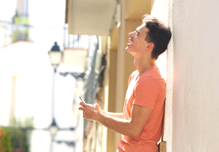 holding cell: Side portrait of a handsome young man holding mobile phone and laughing Stock Photo