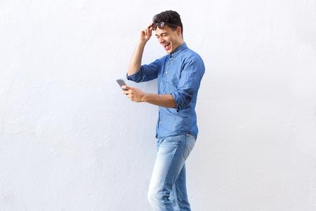 Portrait einer fröhlichen jungen Mann zu Fuß und das Lesen von Text-Nachricht auf Handy