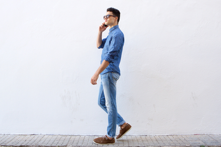 Full body side portrait of a handsome young man walking and talking on cell phone