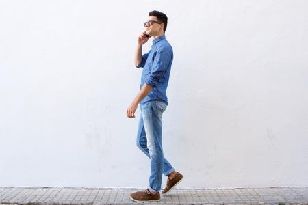 personas en la calle: Todo el cuerpo retrato lateral de un hombre joven y guapo caminando y hablando por teléfono celular