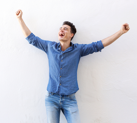 Portrait of a cheerful young man with raised arms celebrating